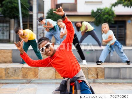 African boy dancing hip-hop with group of tweens on city street 70276003