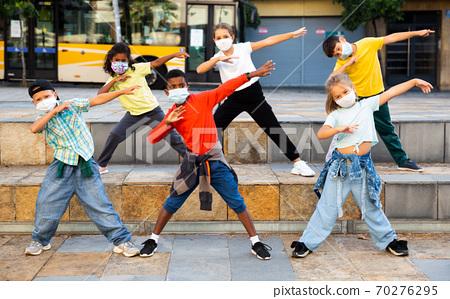Tweens in protective masks dancing hip-hop on summer street 70276295