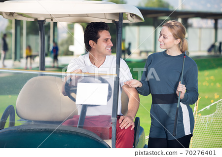 Positive man and woman golfers riding golf cart 70276401