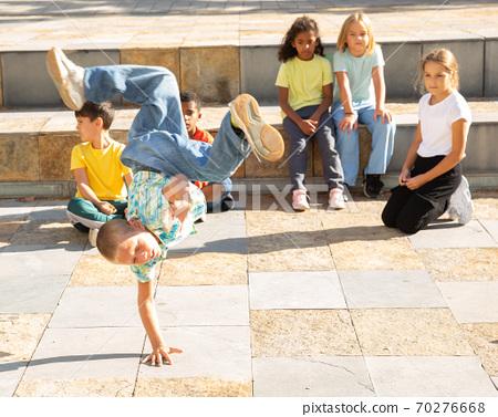 Preteen boy street breakdancer performing acrobatic elements 70276668