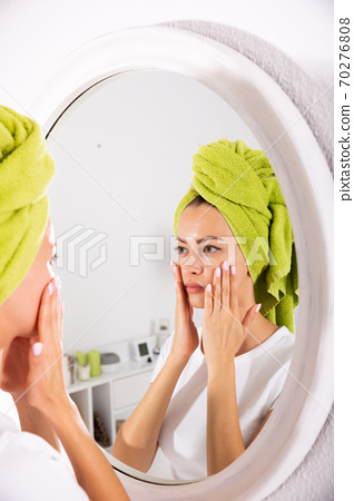 Woman touching her face 70276808