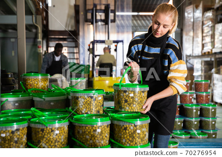 Female worker stocks plastic containers and cans with olives in warehouse 70276954