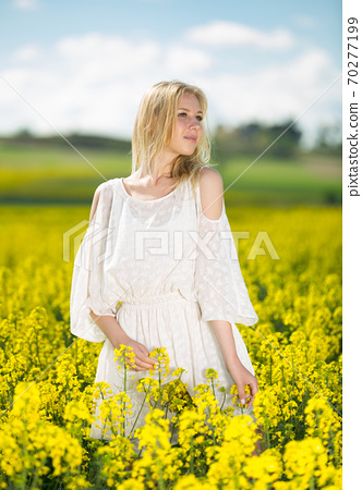 Girl posing in rape seed flowers field posing in white dress at sunny day 70277199