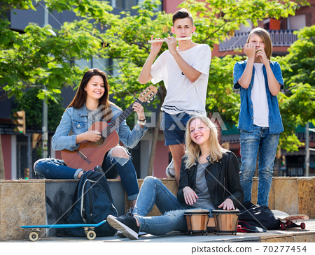 Teenagers friends playing musical instruments 70277454