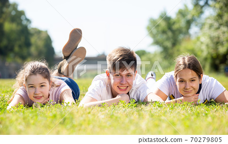 Smiling teenage boy and girls lying on green grass 70279805