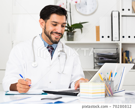 Young man doctor is working behind laptop and reading documents 70280812