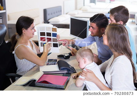 Smiling saleswoman is showing to young family the patterns of ma 70280873