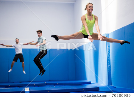 Woman jumping in trampoline center 70280989