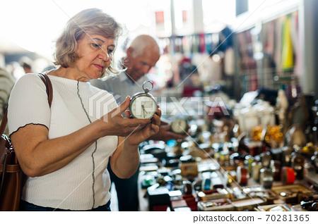 Loving mature couple buys alarm clock on flea market 70281365