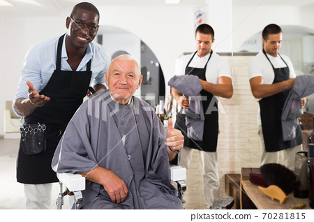 African barber showing result to satisfied elderly client 70281815