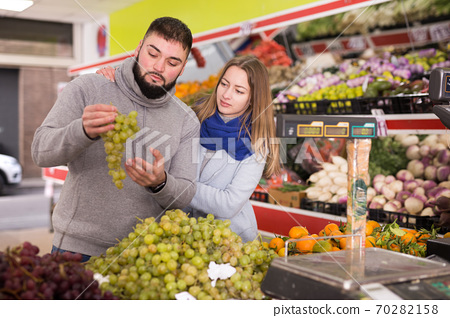 Young couple picks grapes at the grocery store 70282158