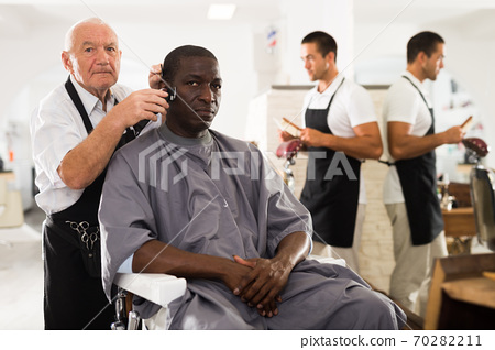 African man getting haircut from elderly barber 70282211
