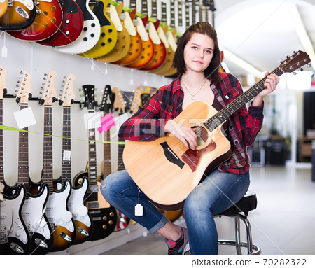 Smiling girl examining various acoustic guitars 70282322