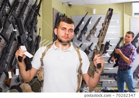 Male is choosing pneumatic gun 70282347