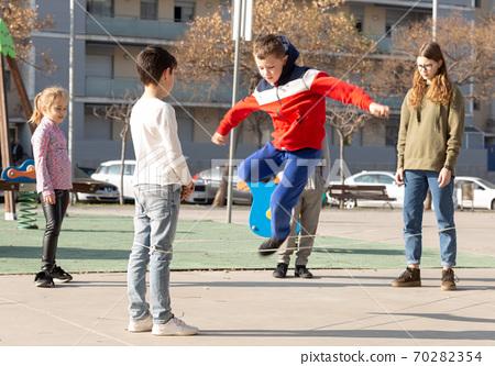 Children skipping on elastic jump rope 70282354