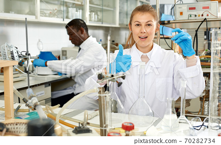 Woman scientist working in research laboratory with collegues 70282734