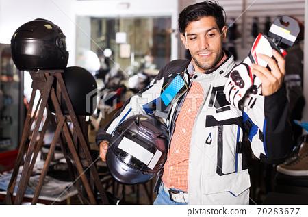 Man choosing moto gloves 70283677