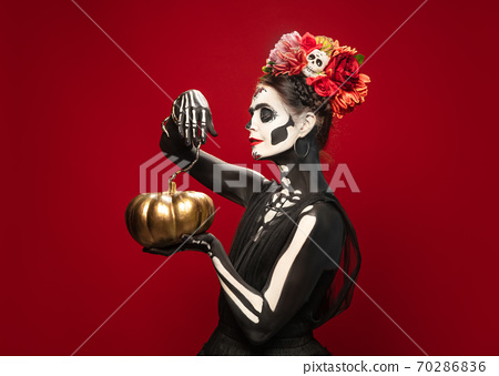 Young girl in the image of Santa Muerte, Saint death or Sugar skull with bright make-up. Portrait isolated on studio background. 70286836