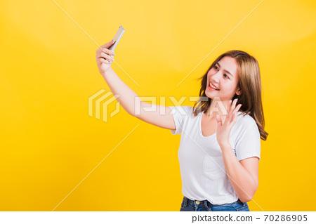 woman teen smiling standing wear t-shirt making selfie photo, video call on smartphone 70286905