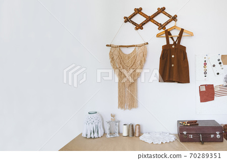Cute Nursery Decorating Ideas, Baby Room Designs decor. Toddler baby Organic cotton clothes hanging on the rack and rustic retro accessories on white wall. 70289351