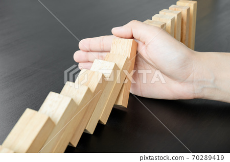 Hands of businesswoman stop block a wood game, gambling placing a wooden block. Concept Risk of management and strategy plan, protect business to success 70289419