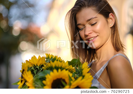 Young fashion  woman with a bouquet of sunflowers in the city 70290725