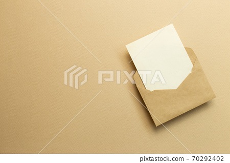 Blank card in kraft envelope on beige background. top view, copy space 70292402