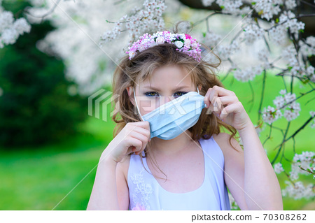 Teenager girl in medical mask in spring flowering garden. 70308262