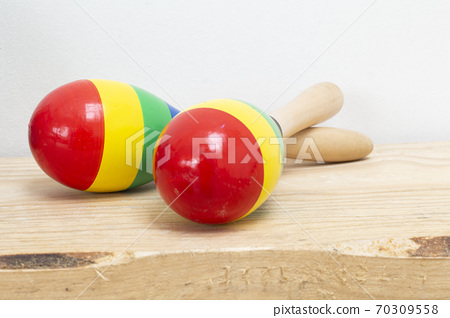 Colorful wooden Mexican Maracas on wooden shelf and white background, beautiful instrument 70309558