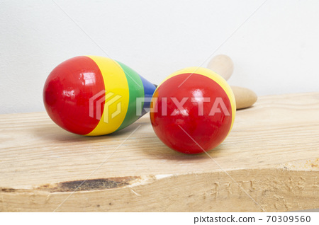 Colorful wooden Mexican Maracas on wooden shelf and white background, beautiful instrument 70309560