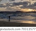 A surfer who finished surfing and the sea where the beautiful sunset sets 70313577