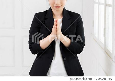 一個年輕的女商人,要求您將雙手放在胸前 70320145