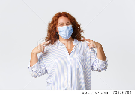 Covid-19 social distancing, coronavirus preventing measures and people concept. Cheerful smiling redhead middle-aged woman staying protected from virus, pointing at medical mask 70326784