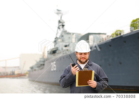 Marine assistant engineer talking by walkie talkie radio and standing near vessel with documents in hands. 70338808