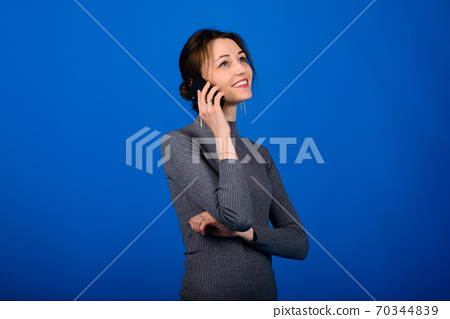 Photo of smiling, cheerful young female in grey dress on blue background 70344839
