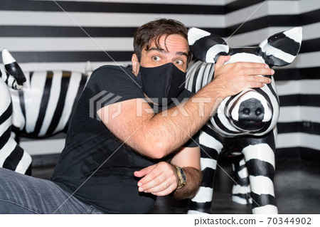 Persian man with mask protecting and covering eyes of his piggy friend 70344902