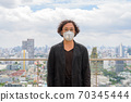 Portrait of Japanese businessman wearing mask against view of the city 70345444