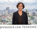 Japanese businessman with curly hair wearing suit against view of the city 70345445