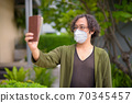 Japanese man with mask taking selfie in the rooftop garden 70345457