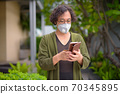 Japanese man with mask using phone in the rooftop garden 70345895