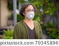 Japanese man with curly hair thinking while wearing mask in the rooftop garden 70345896