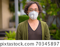Japanese man with curly hair wearing mask in the rooftop garden 70345897