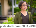 Portrait of Japanese man with curly hair thinking in the rooftop garden 70345898