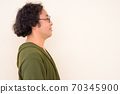 Profile view of happy Japanese man with curly hair smiling 70345900