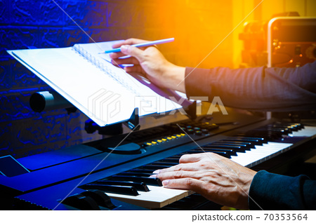 male musician, composer playing piano and writing a hit song in home studio. song writing concept 70353564
