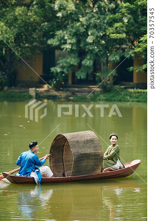 Asian couple rowing small boat 70357545