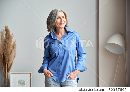 Smiling confident mature older woman standing indoors looking at window. 70357695