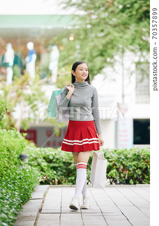 Girl walking outdoors with paper-bags 70357899