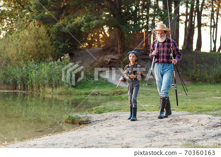 Happy excited boy with his experienced old grey-bearded granddad going near the lake with rods while fishing at sunset. 70360163