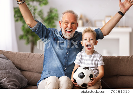 Excited grandfather and grandson watching football match on TV. 70361319